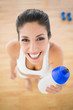 Fit smiling woman holding sports bottle