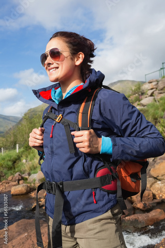 Brunette wearing rain jacket and sunglasses smiling