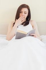Yawning girl reading a book lying on a bed