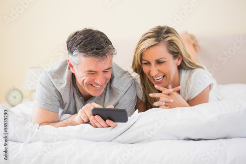 Happy couple lying on a bed and watching a mobile phone