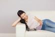 Pretty asian girl lying on the sofa reading a magazine