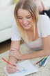 Happy woman lying on floor sketching on paper