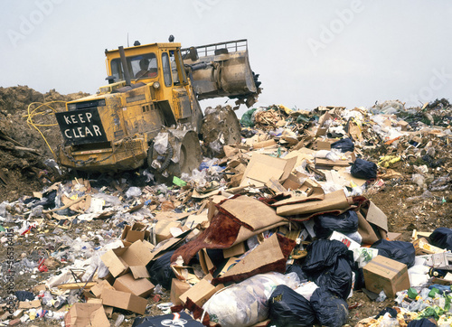 Rubbish tip at landfill site with compactor tractor