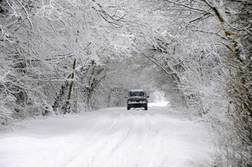 Car driving through snow covered country lane