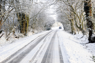 Distant car driving along snow covered country lane