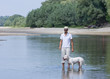 Owner and his dog play in shallow water