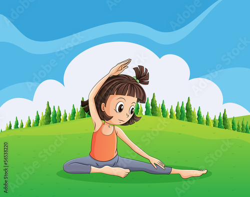 A young girl doing yoga at the hilltop