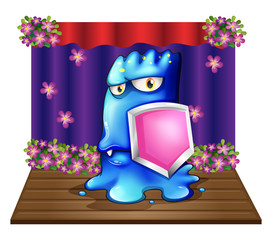 A blue monster at the stage holding a shield
