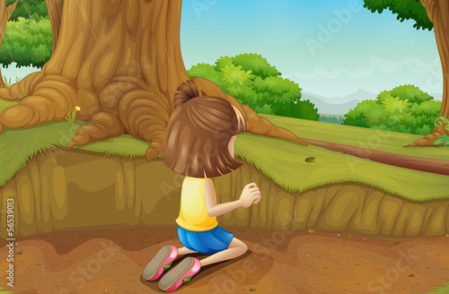 A young girl playing at the ground in the forest