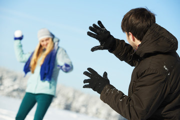 young peolple playing snowballs in winter