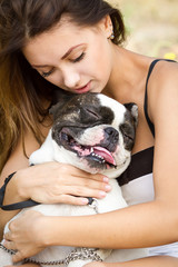 Attractive young girl holding her bulldog