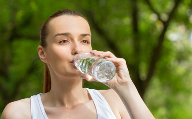 Thirsty woman drinking fresh water, outdoors