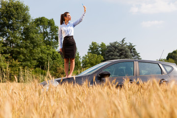 Businesswoman searching phone signal while standing on her car