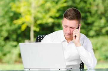 mann schaut auf sein laptop und telefoniert
