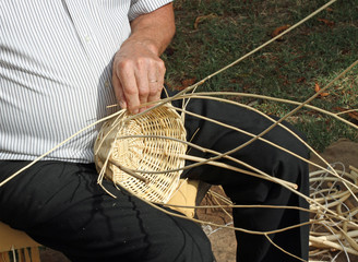 Master strawbedder line while working with hands a wicker dress