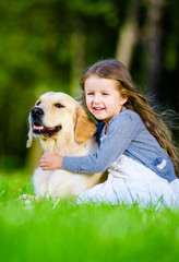 Little girl sitting on the grass with labrador