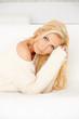 Beautiful blond woman lying on sofa