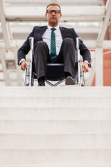 Businessman on wheelchair in front of stairs