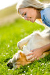 Close up of woman who strokes golden retriever lying on grass