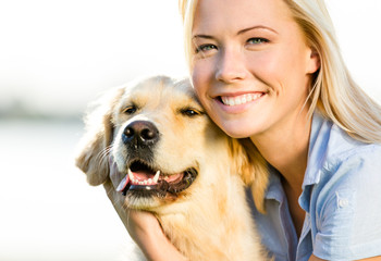 Close up of blond woman embracing golden retriever