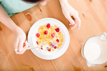 Top view of hands of the girl eating cereals
