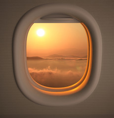 Airplanes window seat view with sunset/sunrise