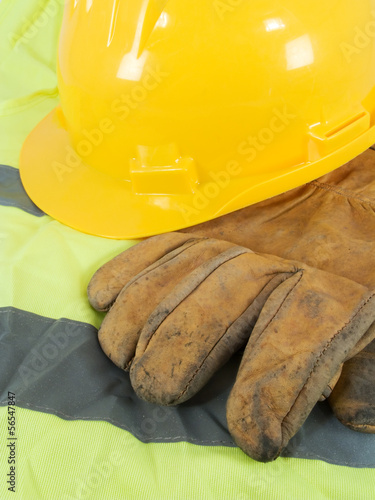 Yellow hardhat, old leather gloves and reflective vest