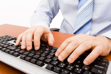Man typing in the computer keyboard.