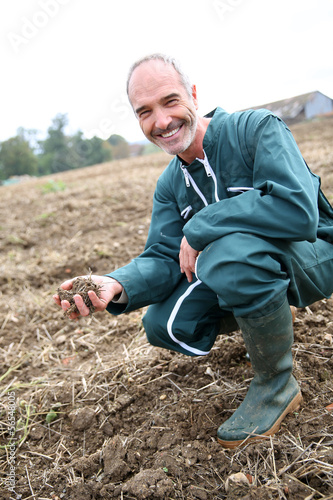Farmer in agricultural field looking at ground quality