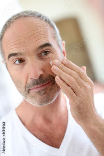 Mature man in front of mirror applying cosmetics