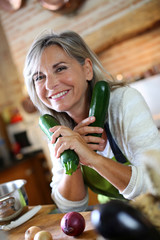 Senior woman in kitchen holding zucchini