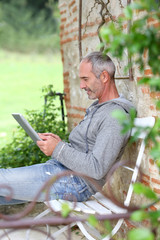 Mature man using tablet on a bench in countryside