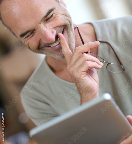 50-year-old man using digital tablet