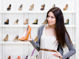 Woman keeping brown leather shoe in shopping center