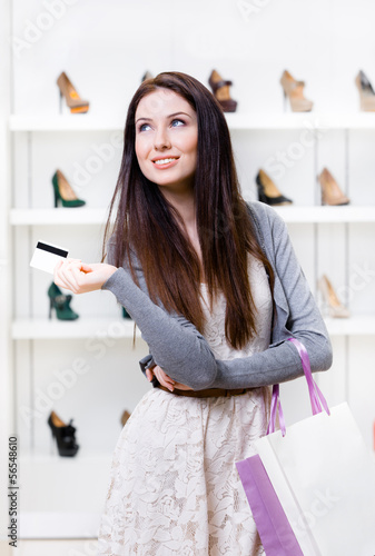 Female hands credit card in footwear shop