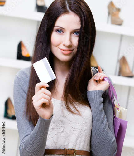 Female holds credit card in the shop with variety of shoes