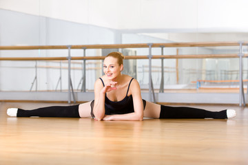 Ballerina does the splits sitting on the floor