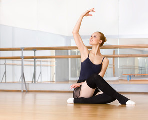 Ballerina works out sitting on the floor in the classroom
