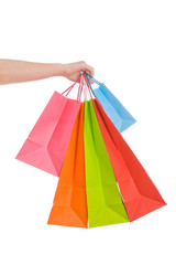 Woman hand holding several shopping bags isolated on white.