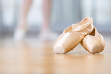 Close up of pointes for ballet lying on the wooden floor