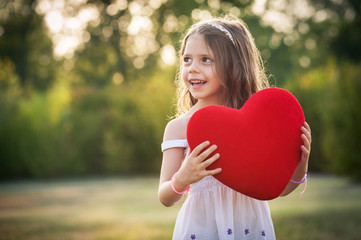 Sweet girl with red heart outdoors in the park.