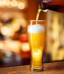 pouring beer in glass on bar or pub desk