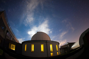 Astronomical observatory dome in the night with stars and glowin