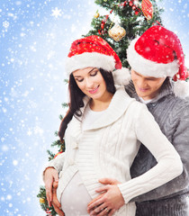 A young and pregnant mother and a father in Christmas hats