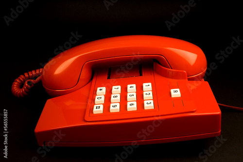 Red telephone on a black background