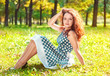 Beautiful young woman sitting on the grass