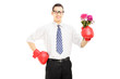 Smiling man with boxing gloves holding a bunch of flowers