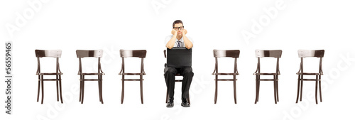Bored man sitting on a chair waiting for job interview