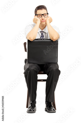 Sad male with leather suitcase sitting on a wooden chair