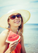 Young stylish lady at sea with watermelon